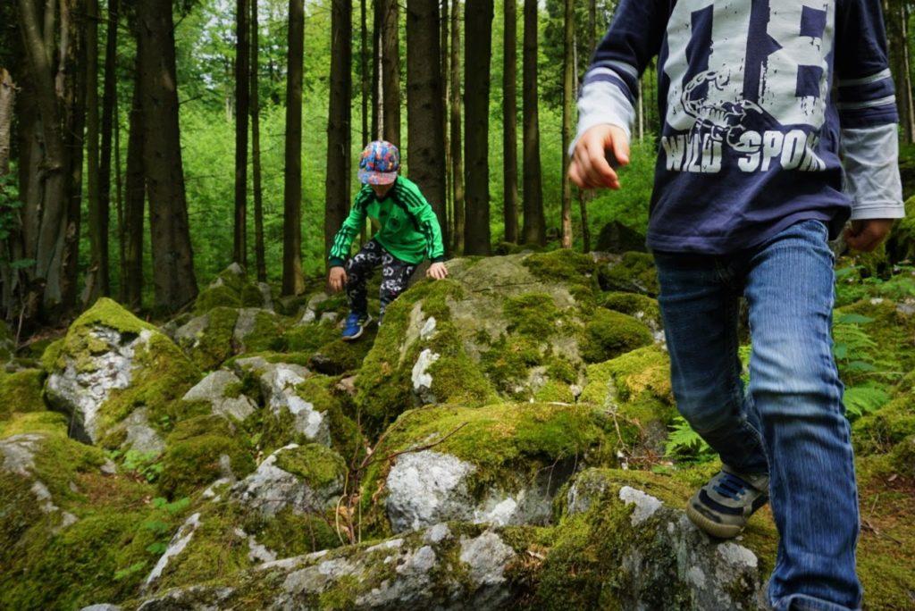 Kinder klettern über Felsen