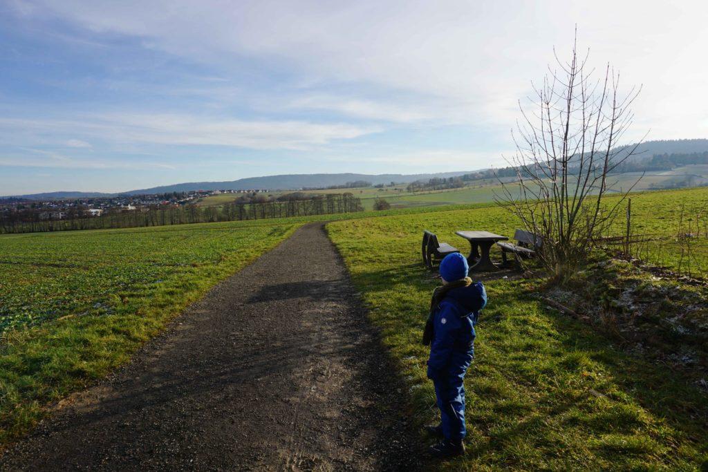 Kind steht am Weg und schaut ins Tal