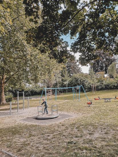 Kind auf Kinderkarussel auf dem Spielplatz