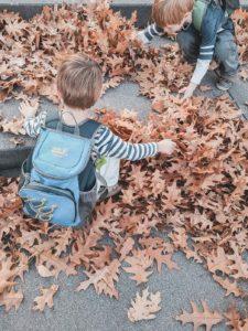 Kinder spielen im Herbst mit Blättern