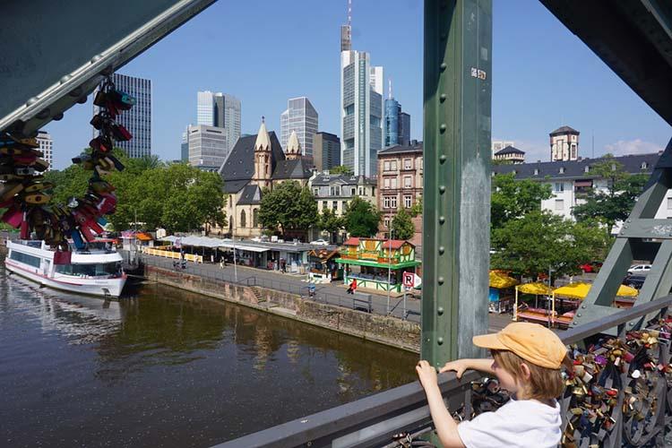 Kind blickt vom Eisernen Steg auf die Skyline Frankfurt